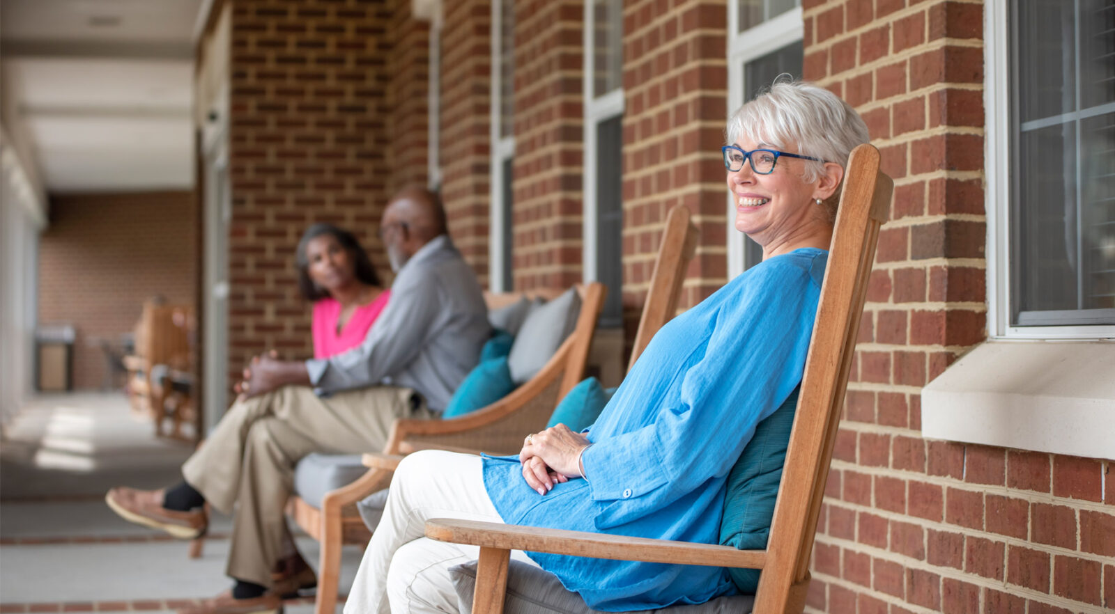 A woman sitting in a rocking chair on the front porch of her apartment unit.